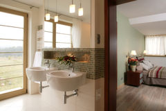 Stylish Bathroom and Bedroom. A stylish en-suite bathroom with two wash basins. Doorway leads to a bedroom decorated in a contemporary style stock photo
