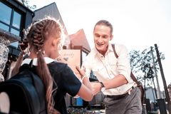 Stylish beaming father making his cute schoolgirl birthday surprise royalty free stock photo