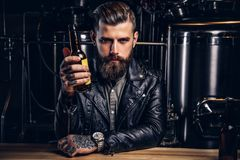 Stylish bearded biker dressed black leather jacket sitting at bar counter in indie brewery. stock photos