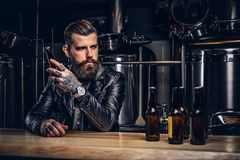 Stylish bearded biker dressed black leather jacket sitting at bar counter in indie brewery. royalty free stock photos