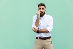 Stylish bearded businessman with warried. Hipster guy having shocked face, looking at camera. Indoor, studio shot,. Light green background Stock Image