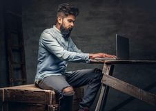 Stylish  Indian male working with laptop. Stylish bearded Indian male working with laptop Stock Photos