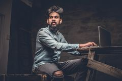 Stylish  Indian male working with laptop. Stylish bearded Indian male working with laptop Stock Photo