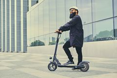 A man posing on electric scooter. Stylish bearded male in sunglasses posing on electric scooter in over modern building background Royalty Free Stock Images