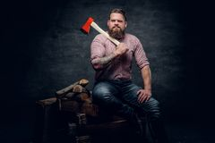 Bearded man wearing pink plaid shirt and holds an axe. Stylish bearded male with tattoos on arms wearing pink plaid shirt and holds an axe Stock Images