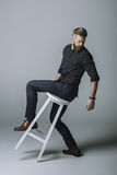 Stylish bearded man posing on chair Stock Images