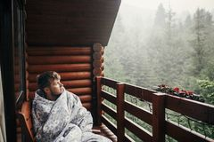 Stylish bearded man relaxing on wooden porch among forest in rai. Ny mountains. hipster guy resting in blanket, sitting in cottage, looking at rain. calm Stock Image