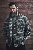 Stylish bearded man. Style. Bearded man in camouflage jacket is looking at camera while standing with his hands in pockets on a wooden background royalty free stock photo