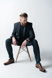 Stylish bearded man in suit sitting on chair Stock Photo