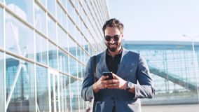 Stylish bearded man in sunglasses using device while passing by the airport terminal, smiles to the received text