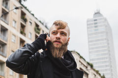 Stylish bearded man talking on phone Stock Images