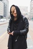 Stylish bearded man texting in the street Stock Photo