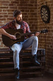 Stylish bearded musician. Handsome young bearded musician in casual clothes is playing a guitar, sitting against brick wall stock photos