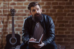 Stylish bearded musician. Young bearded man in black leather jacket is making notes and looking away, sitting against brick wall, a guitar in the background royalty free stock photo