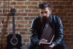 Stylish bearded musician. Young bearded man in black leather jacket is making notes and looking at camera, sitting against brick wall, a guitar in the background royalty free stock photos
