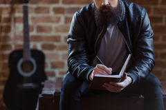 Stylish bearded musician. Young bearded man in black leather jacket is making notes, sitting against brick wall, close-up. Guitar in the background royalty free stock image