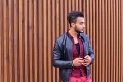 Stylish bearded young man holding in hands and uses smart phone, Stock Images