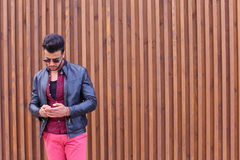 Stylish bearded young man holding in hands and uses smart phone, Stock Photo