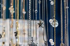 Stylish beautiful bijouterie hanging on the stand in the accessories store. Various Jewelry bijouterie show in retail shop window royalty free stock photos