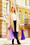 Stylish, beautiful blonde hair smiling girl with shoppings. Happy shopping. Stock Photos