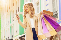 Stylish, beautiful blonde hair smiling girl with shoppings using her phone. Happy shopping. Stock Images