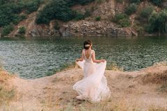 Stylish, beautiful bride posing in a luxurious dress against the backdrop of a sunset and a river. Photo from the back. Stylish bride posing in a luxurious dress royalty free stock image