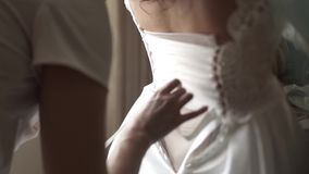 Stylish beautiful bridesmaids helping gorgeous brunette bride in white dress get ready for wedding, morning preparations stock video footage
