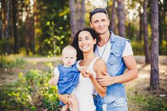 Stylish beautiful fashionable parents are holding a girl in the park on the background of a dense forest. royalty free stock photography