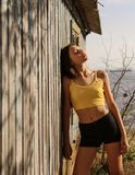 Beautiful brunette with a little red hair model posing in yellow top and red snikers outside. Nature concept. Stylish beautiful girl in colorful clothes: yellow Royalty Free Stock Photo