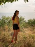 Beautiful brunette with a little red hair model posing in yellow top and red snikers outside. Nature concept. Stylish beautiful girl in colorful clothes: yellow Stock Image