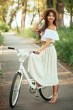 Stylish and beautiful girl does not bike with flowers royalty free stock photography