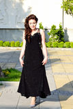 Stylish beautiful girl. Happy beautiful nineteen years old girl school leaver dressed in brilliant black ball gown going to her Prom day party stock images