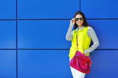 Stylish beautiful girl standing near blue wall Royalty Free Stock Photos