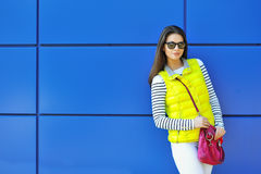 Stylish beautiful girl standing near blue wall Stock Photography