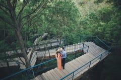 Stylish beautiful happy wedding couple kissing and embracing in Botanical Garden.  Royalty Free Stock Photo