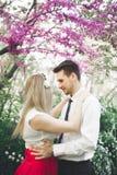 Stylish beautiful happy wedding couple kissing and embracing in Botanical Garden.  Stock Photos