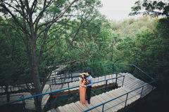 Stylish beautiful happy wedding couple kissing and embracing in Botanical Garden.  Stock Images