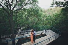 Stylish beautiful happy wedding couple kissing and embracing in Botanical Garden.  Royalty Free Stock Photos