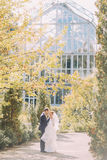 Stylish beautiful happy wedding couple kissing and embracing in Botanical Garden. Sunny summer day Stock Image
