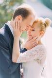 Stylish beautiful happy wedding couple kissing softly embracing in Botanical Garden Stock Photo