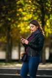 Stylish beautiful lady in a black leather jacket with a black bag and brown fur. using a phone royalty free stock image