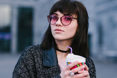 Stylish and beautiful smiling girl in pink hipster glasses holding a cup of coffee on blurred background. Stylish and smiling girl in pink hipster glasses Stock Photos