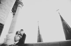 Stylish beautiful wedding couple kissing and hugging on background panoramic view of the old town Royalty Free Stock Image