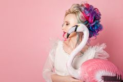 Stylish and beautiful woman with colored hair. Hugging a pink Flamingo figure. Stock Images