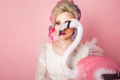 Stylish and beautiful woman with colored hair. Hugging a pink Flamingo figure. Stock Photos