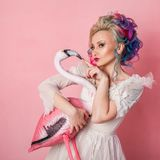 Stylish and beautiful woman with colored hair. Hugging a pink Flamingo figure. Royalty Free Stock Photos