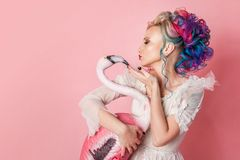 Stylish and beautiful woman with colored hair. Hugging a pink Flamingo figure. Royalty Free Stock Image