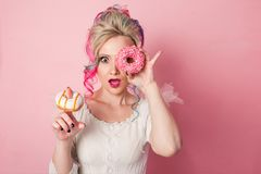 Stylish and beautiful woman with colored hair. Two donuts as glasses, funny grimace Royalty Free Stock Photo