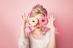Stylish and beautiful woman with colored hair. Two donuts as glasses, funny grimace Stock Image