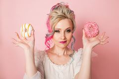 Stylish and beautiful woman with colored hair with Two donuts, glamour pink style Royalty Free Stock Photo